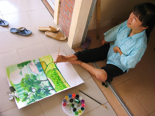 Sum, a residant of a training facility outside of Ho Chi Minh City specifically designed for persons effected by Dioxin, is an artist that paints with her feet.