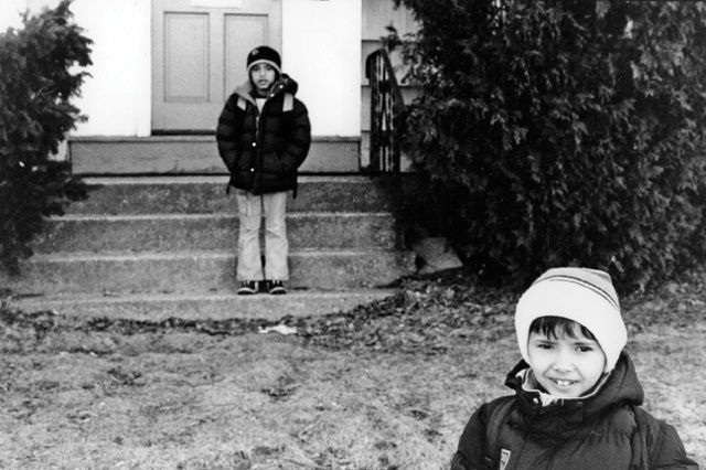 Faysel's sons wait for the bus outside of their house in Portland, Maine.