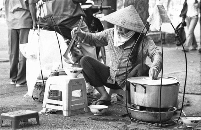 A woman prepares Pho on the street in downtown Saigon.