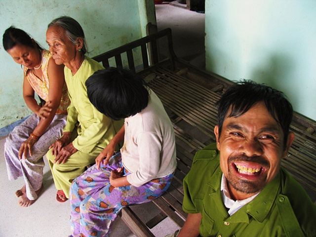 A mother sits with her three developmentally disabled children in their home outside of Danang.