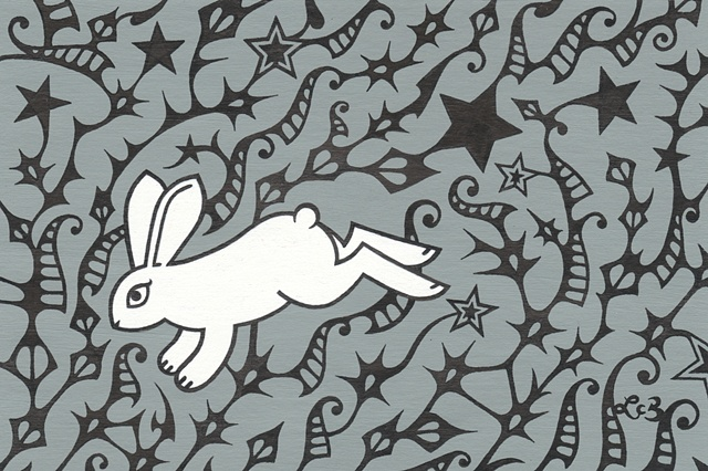 A white rabbit running through the black thorny shapes of star thistles.