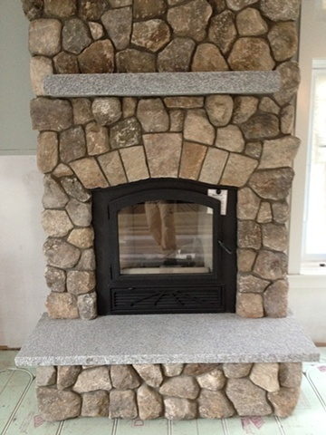 Cut stone arch and granite hearth and mantle