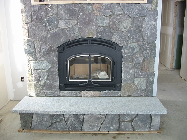 Thin stone veneer around a wood burning fireplace insert.