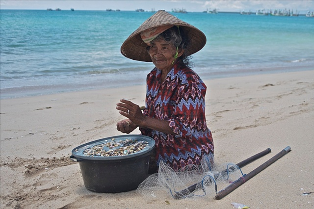 Bali Beach old woman fishing