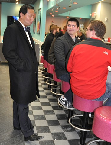 President Santa Ono of University of Cincinnati talking with students at local restaurant, Highway 55