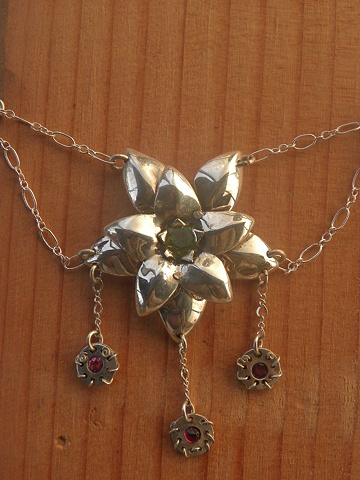 delicate sterling silver flower necklace featuring peridot, ruby, and garnet facets