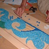 Cutting and gluing the mosaics on the drawn design.