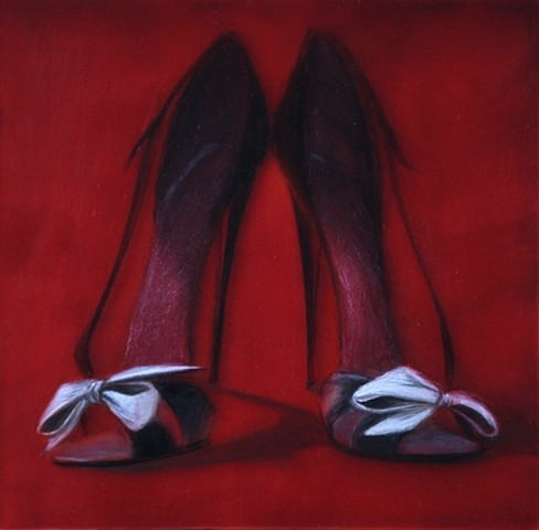 Black strappy high heel shoes, with white bows, and red background.