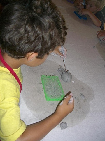 Four year old working on clay project.