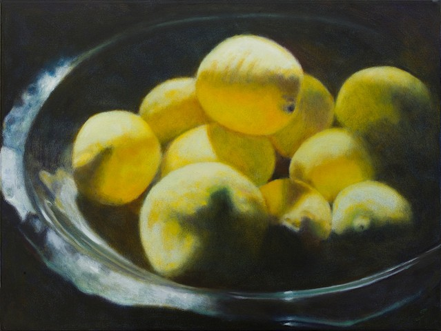 Contrast of strong light on lemons in glass bowl.  Black background  Close up.