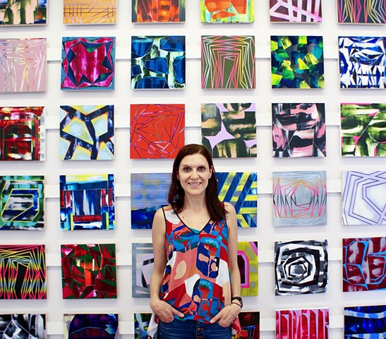 Elyce Abrams in front of paintings from the 100paintings project