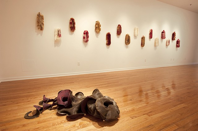 "Wall: Give and Receive series, 2008. Machine-sewn coffee filters and thread, approx. 18"" x 10"" x 4 ½""each. Floor: Medusa, 2008. Machine-sewn zippers, dimensions variable."