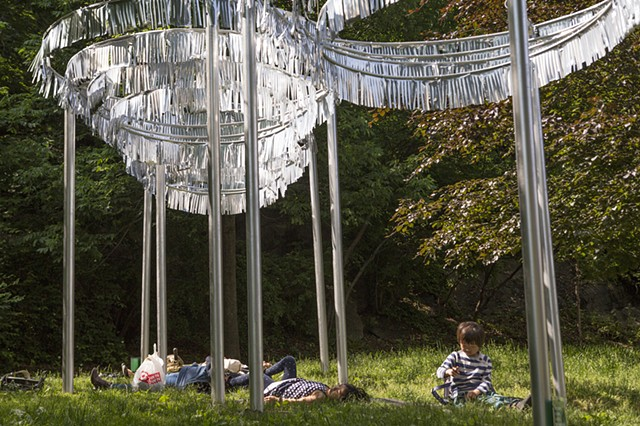 "Visitors lounging under ""Reflections: Path"""