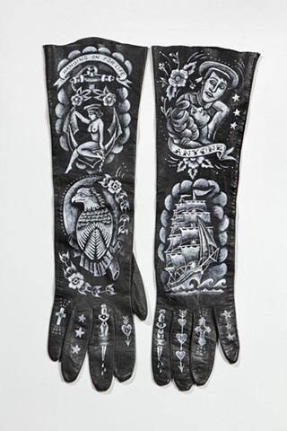 traditional tattoo designs on vintage leather gloves with sailor motifs