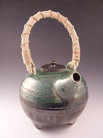 Three-legged tripod teapot with cane handle.