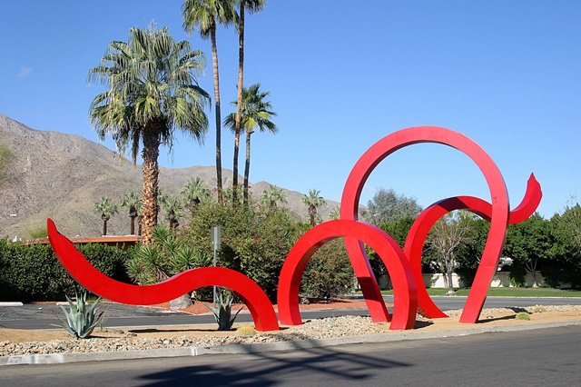 """A monumental outdoor sculpture, """"Jungle Red"""" is composed of large red fabricated steel beams that appears to move in and out of the ground in both a dramatic and whimsical style."""
