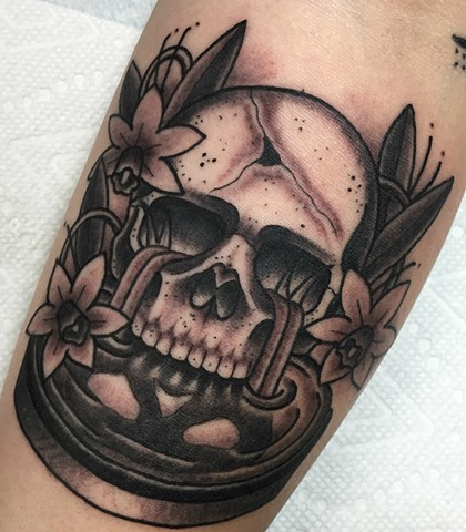 Black and grey traditional skull tattoo with daffodil flowers and water. Made in Toronto