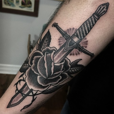Scottish dagger through a classic black and grey rose tattoo on the arm, made in Toronto