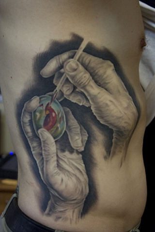 Hands Painting Egg Tattoo on ribs