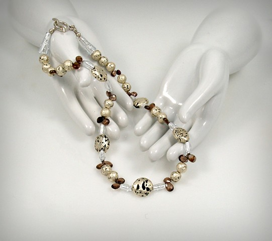 "Jan Maitland Jewelry, ""Sweet Sapphire"" Necklace  Hand-gilded White Gold Leaf on Lava, Brown Sapphires, Czech Glass, and Sterling Silver Toggle Clasp, and Artist's Signature Tag. Measures 18.5"""