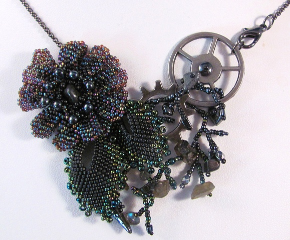 Purple flower with black and green leaves, hematite chips and gun metal findings
