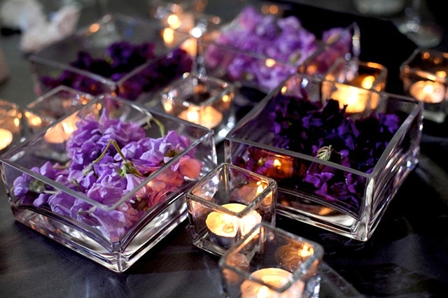 "4"" Clear glass ""trays"" (2"" height) in a geometric configuration, filled with light and dark purple stock blooms, and surrounded by votives and tea lights."