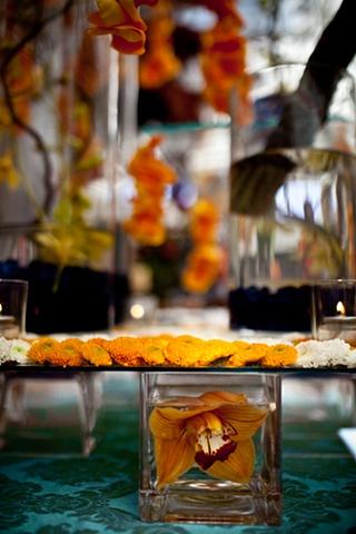 Blue World StudiosModern Orange Tablescape Detail Hanging rose petals
