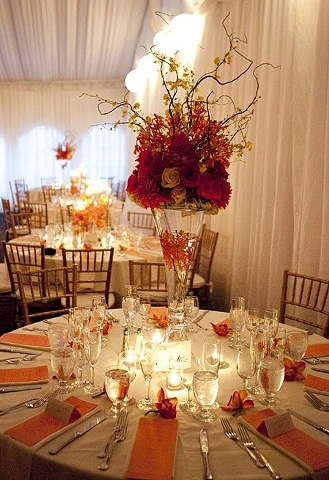 Orange, yellow, and hot pink roses, orange dahlias, orange mokara orchids, yellow oncidium orchids, and curly willow branches.  Tropical Centerpiece in a Reversible Vase