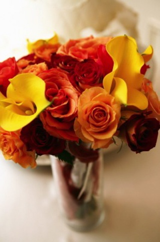 "I Shot the Bride Fall ""Fortune"" Toss Bouquet Lush toss bouquet composed of smaller bouquet clusters of yellow mini calla lilies, and red and orange roses.  Each cluster bears a slip of paper with a written fortune, to be caught by several lucky guests."