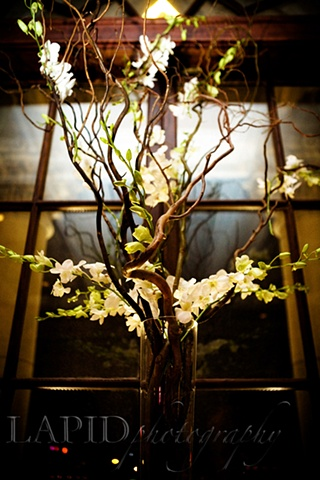Curly Willow Centerpiece Michelle Lapid Photography White dendrobium orchids intertwined in curly willow branches.
