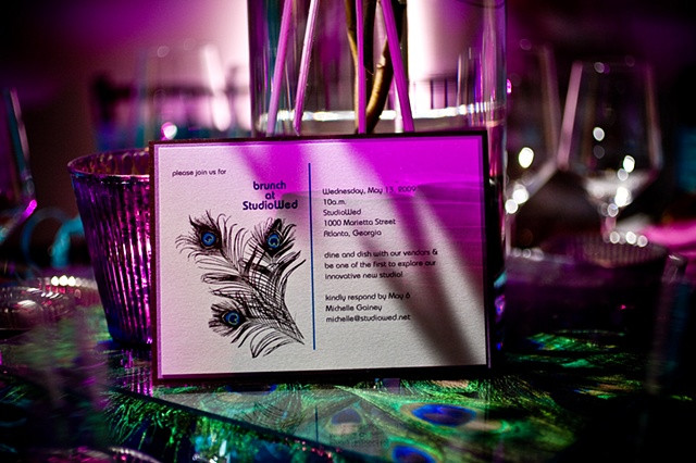 Modern Peacock Tablescape Blue World Studios Customized Placecard, (courtesy of |http://www.inkandpaintonline.com|Ink and Paint|), set on a raised platform of peacock feathers sandwiched between two clear glass sheets