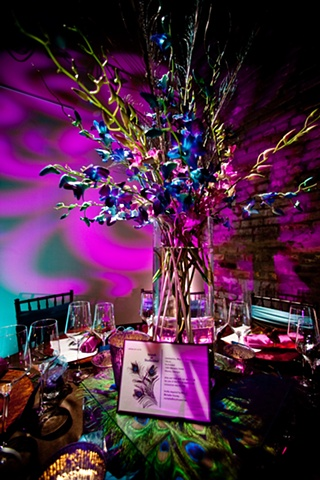 Modern Design - Peacock Tablescape Blue World Studios Peacock feathers and magenta and blue dendrobium orchids in a clear glass cylinder sit on top of a raised platform of peacock feathers sandwiched between two sheets of clear glass.