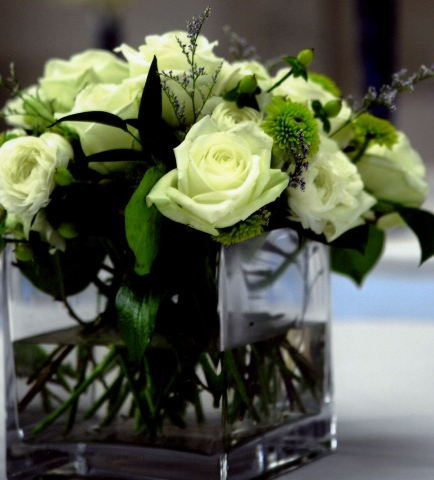 Stacey Bode Photography Low Square Centerpiece White roses, white ranunculus, green button mums, green hypericum, and italian ruscus in a clear, square, vase.