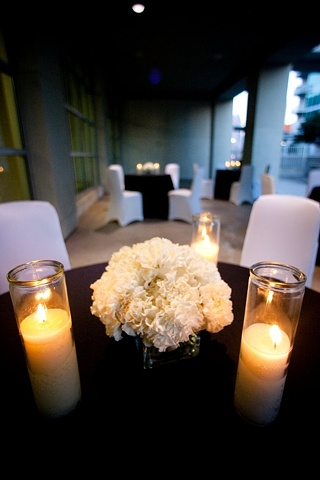 "Mass of white carnations in a 4"" clear glass cube are flanked by 8"" candles to accent an outdoor guest table.  Modern Design - Low Carnation Centerpiece"