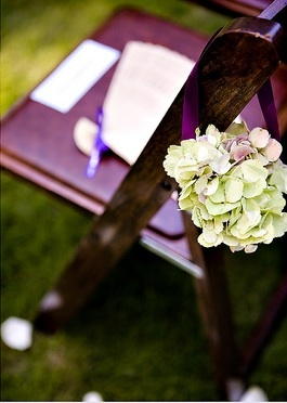 Stacey Bode Photograph Aisle marker composed of green hydrangea blooms in a paper cone, hanging from a purple satin ribbon.