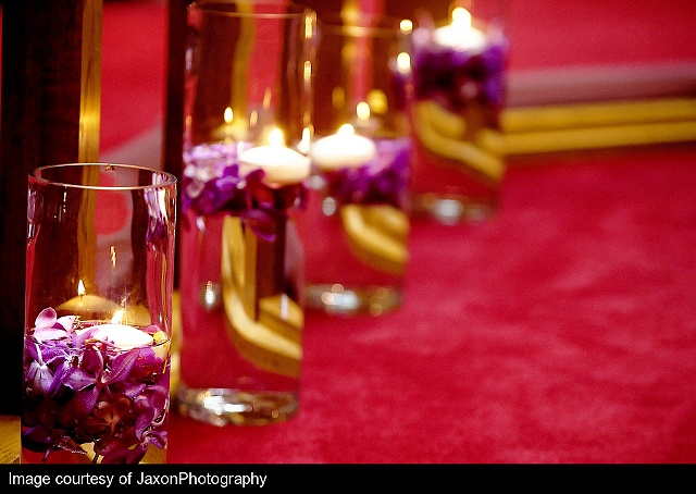 Jaxon Photography Floating Candle Aisle Decor Floating purple mokara orchids in cylinders of various heights lining the aisle.
