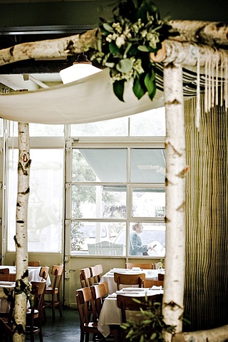 Stacey Bode Photography Self-standing birch chuppah draped with a tallis, and accented with a cluster of greenery composed of lemon leaf and seeded eucalyptus.