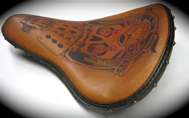 Tattooed leather motorcycle seat.