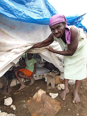 Woman showing her tent camp home Léogâne