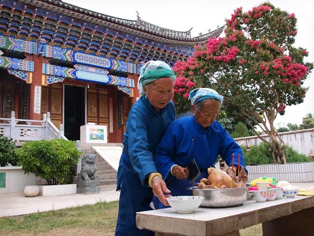 Two women preparing sacrifice to temple idols