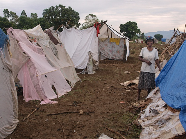 Woman in Leogane tent camp among shelters from bed sheets