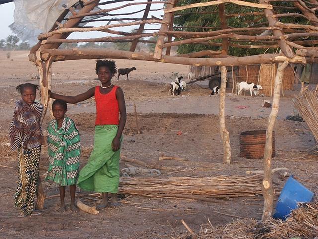 Children under the frame of a hut