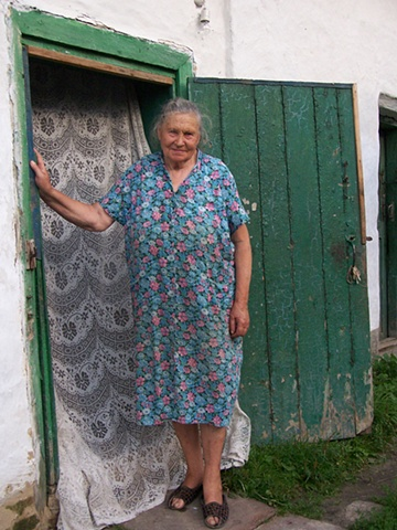 Olya in the doorway of her home