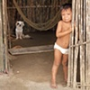 Child in doorway with dog San Blas Islands