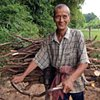 Villager pushing bicycle loaded with wood