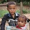 Boy carrying sister in handlebar basket