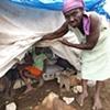 Woman showing her tent camp home Léogâne