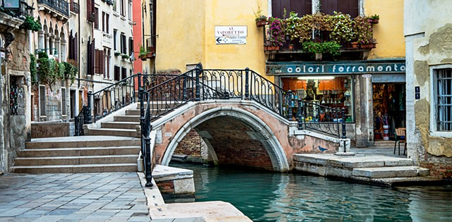 Yellow stucco by turquoise waters of a Venice Canal