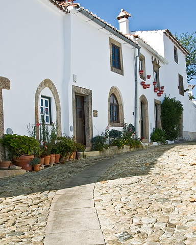 A walled medieval town in the mountains in Portugal , all in white stucco