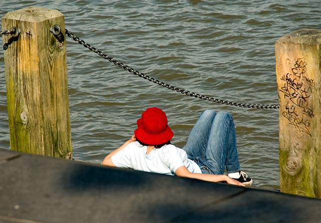 Person sitting on the steps of the River in New Orleans in a red hat watching the world go by
